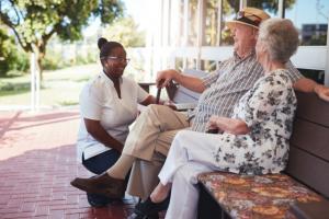 senior couple talking to caregiver